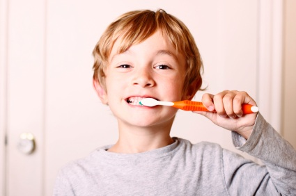 A boy brushing his teeth happily.