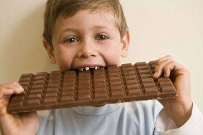 A young boy damaging his oral health by eating to many sweets!