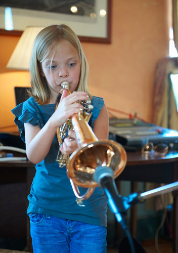 A young girl blowing into a trumpet.
